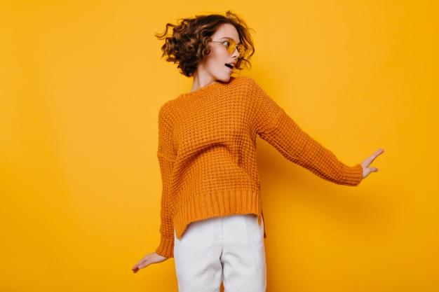 mujer con jersey mostaza y pantalón blanco sobre fondo amarillo.