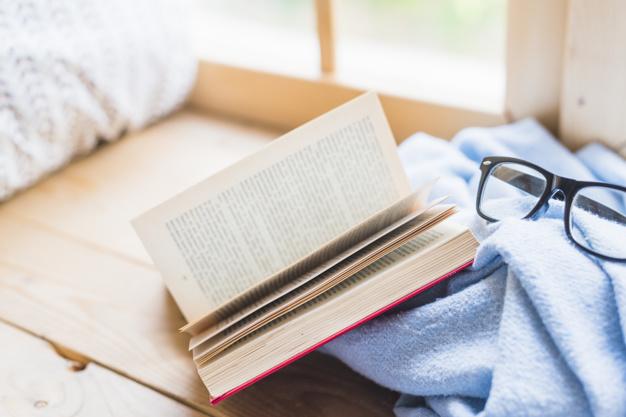 libro abierto, manta y gafas