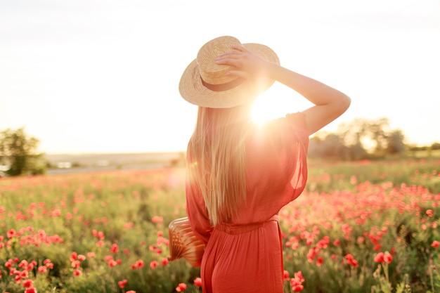 mujer mirando al campo con vestido rojo y sombrero